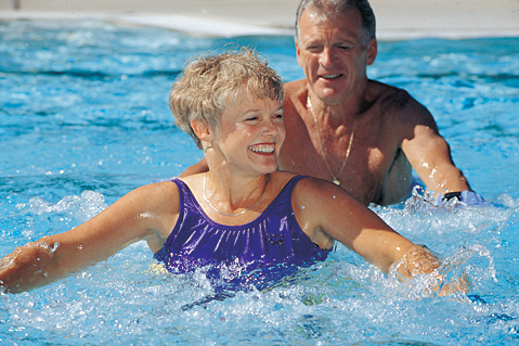 Active aging Man and Woman couple performing water exercises with AquaJogger equipment in a swimming pool. The woman is wearing a purple swimsuit and smiling. The man is wearing a gold neck chain and seems winded.